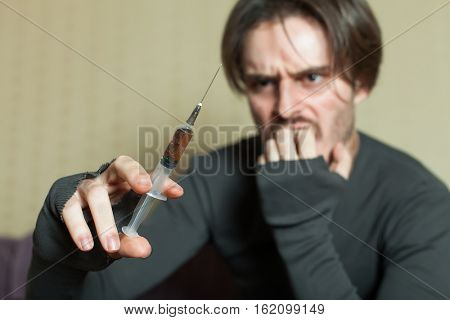 Abuse addict man with syringe in hand.