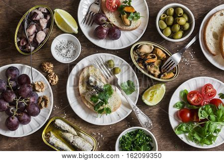 Snacks table - canned sardines mussels octopus grape olives tomato on wooden table top view. Flat lay