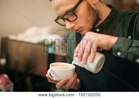 Closeup of male hands adding cream to coffee.