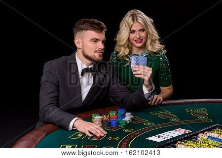 View of young, confident, man with the lady while he's playing poker game.Man bets in poker