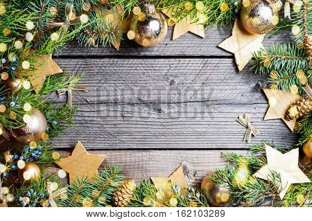Christmas background. Green Fir tree branches with pine cones, gold snowflakes, ball, stars and bokeh on wooden background. Copy spase inside