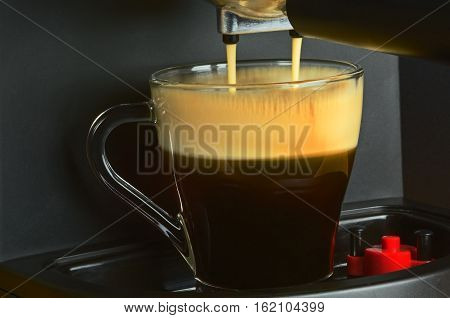 Very close view on coffe machine pouring espresso in the interesting atmospheric light with clearly visible slightly not sharp rivulets pouring coffee and a foam on its surface Horizontal view.