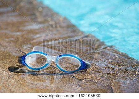 blue swimming goggles isolated on swimming pool edges and clear blue water background with copy space