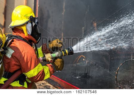 firefighter hold and adjust nozzle and fire hose spraying high pressure water in fire fighting operation
