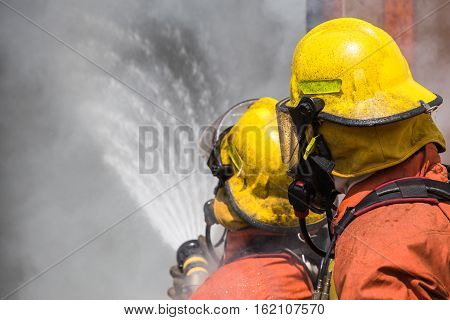 two firefighter buddies in helmet and oxygen mask spraying water to fire surround with smoke and dust