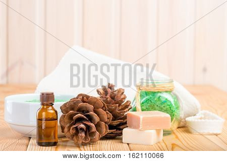 pine essential oil and bath salts close up on wooden boards