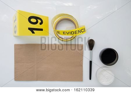evidence marker tape and brown paper bag with latent fingerprint searh for crime scene isolated with blank and copy space