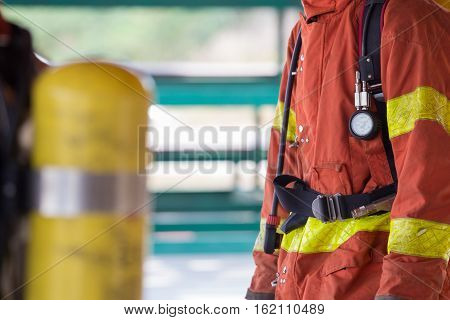 close up fireman in fire fighting protection suit and equipment standby for operation