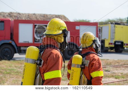 2 firefighters in fire protection equipment and fire truck background