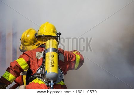 firefighter and rescue team in fire protecction suit and equipment work surround with smoke and dust