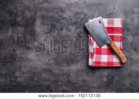 Butcher. Vintage butcher meat cleavers with cloth towel on dark concrete or wooden kitchen board.