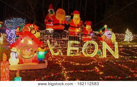 An outdoor Christmas light and inflatable decoration display in a yard