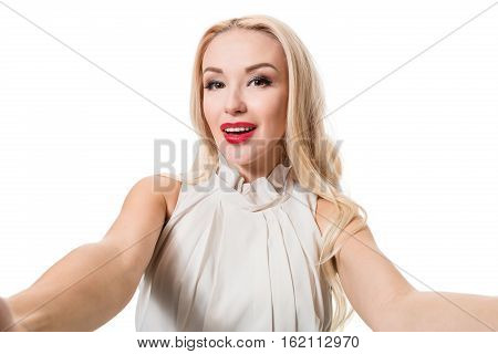 Smiling cheerful blond-haired woman doing selfie on isolated white background. Taking picture.