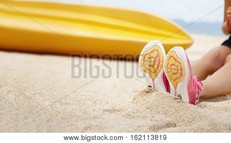 Cropped Shot Of Female Athlete Wearing Pink Running Shoes Sitting On Sandy Beach After Active Exerci