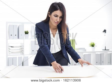 Woman Architect Working With Blueprints While Standing Near Her Desk