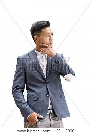 Isolated portrait of a young Asian businessman with his hand in a pocket. He is rubbing his chin and thinking