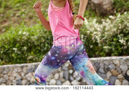 Endurance And Determination. Determined Female Runner In Stylish Sportswear Running In City Park. Mi