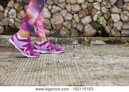 Sports And Healthy Lifestyle. Close Up Of Woman's Legs In Stylish Purple Sneakers And Space Print Le