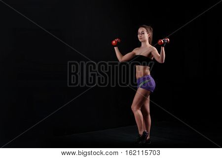 Sport girl holding a dumbbell on a black background.