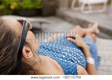 Rear View Of Beautiful Young Woman Expecting Baby Lying On Sunlounger While Spending Nice Time At Sp