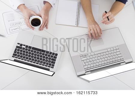 Top view of two pairs of women's hands. One is holding her coffee cup. The second is using her touchpad