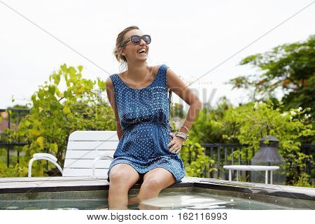 Expectant Mother In Sunglasses Having Happy Smile While Relaxing At Swimming Pool, Her Legs Dangling