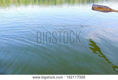 Wooden oar, water drops, and ripples on the surface.