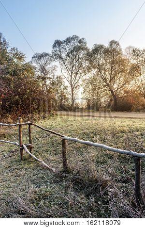 Wooden Fence In Fog On Frozen Meadow At Sunrise
