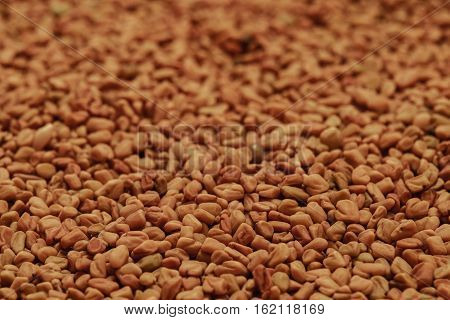 dry fenugreek seeds background on the table