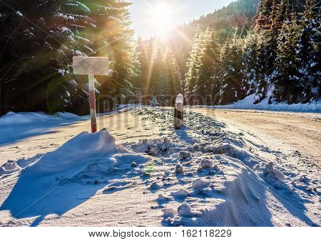 winter mountain landscape. wooden road sign on winding road that leads into the spruce forest covered with snow at sunrise