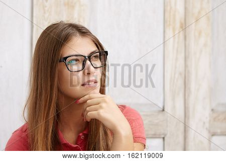 Serious Young Woman In Stylish Rectangular Glasses And Polo Shirt Looking Away With Thoughtful And P