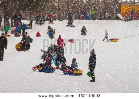 Children having fun tobogganing in the winter down. Selective focus. Concepts of active lifestyles, childhood, Christmas, holiday