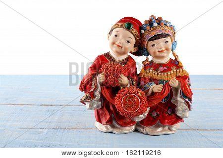 Chinese Wedding Figurines on Wooden Textured Background