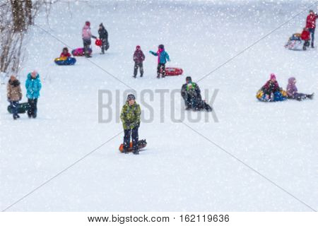 Happy children of sledding down a hill . Concepts active lifestyles, childhood, winter, Christmas. Selective focus. With place for your text