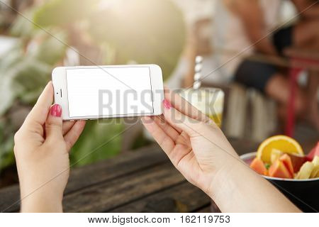Close Up Of Modern Smart Phone In Woman's Hands. Young Female Holding Electronic Gadget, Using Free