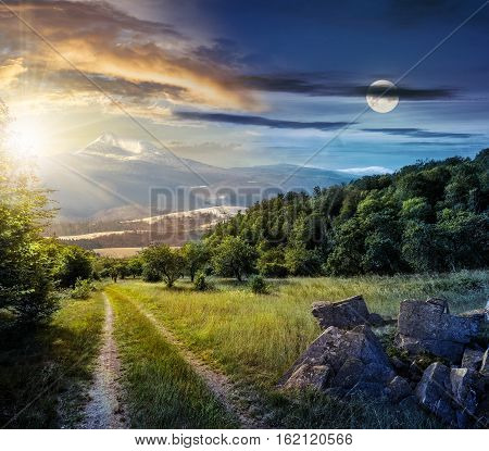 Concept day and night time change. Winter meets spring composite landscape. Valley with trees and boulders on a grass. Road through meadow goes to forest in mountains with snowy peak under cloudy sky