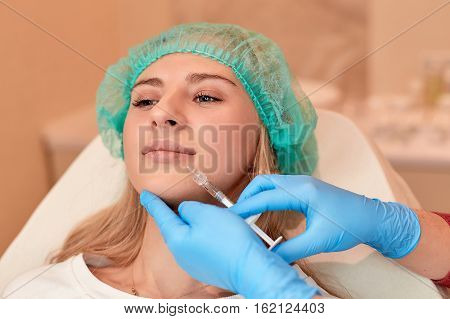 Closeup of beautiful woman gets injection in her lips. Cosmetic injection in the lips of unrecognizable woman, close-up. Beautiful big lips. Plastic and aesthetic surgery
