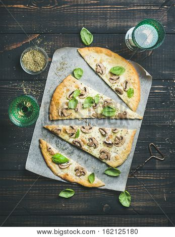 Homemade mushroom pizza with basil cut in slices, spices in glass and rose wine on dark scorched wooden background, top view, vertical composition