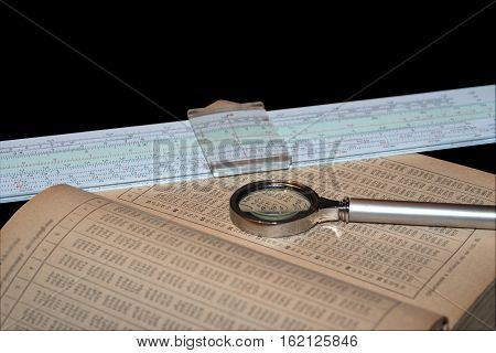 Handbook of mathematics magnifying glass and a slide rule isolated on black background