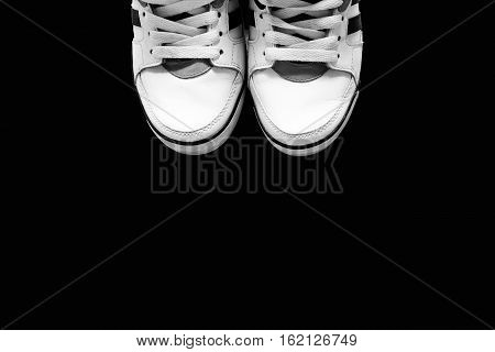The white sports shoes on a blackbackground