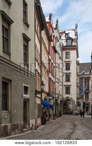 MUNICH GERMANY - JANUARY 01 2011 - Two unidentified elderly people walk along the pedestrian narrow street in the center of Munich