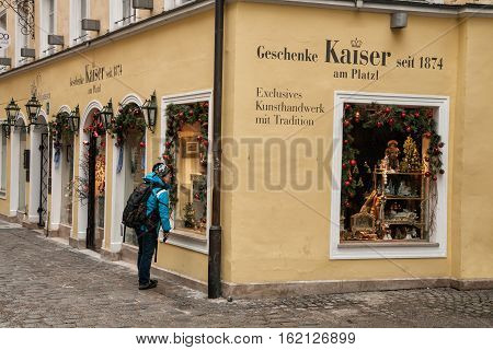 MUNICH GERMANY - JANUARY 01 2011 - A woman looking at shop window Geschenke Kaiser decorated for Christmas