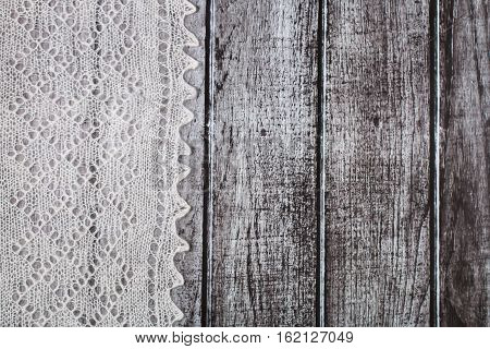 Delicate crocheted handmade woolen downy material over rustic wooden background