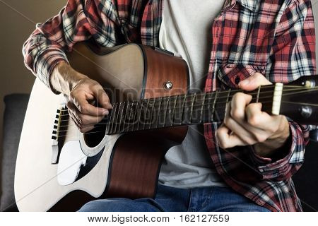 Playing instrument at home. Male hands playing chord on acoustic guitar