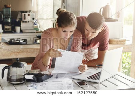 Scenic Young Family Doing Paperwork At Home. Wife Looking Worried Sitting At Kitchen Table With Lot