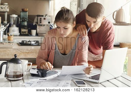 Young Caucasian Family Facing Credit Debt Problem. Beautiful Woman Holding Piece Of Paper And Calcul