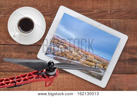 aerial view of Fort Collins downtown, Poudre River and a bike trail on digital tablet with coffee and drone propeller, screen image