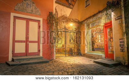 Tallinn, Estonia - November 21st 2016: Street near town hall in Tallinn Estonia, at night. Lovely ancient view with gates and warm lights. Rustic architecture cityscapes landmarks old town patio