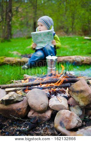 Boy With Map Sitting Near A Campfire.