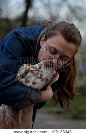 Pure love: young woman wearing glasses kissing pure breed spotty white big dog of hunting breed
